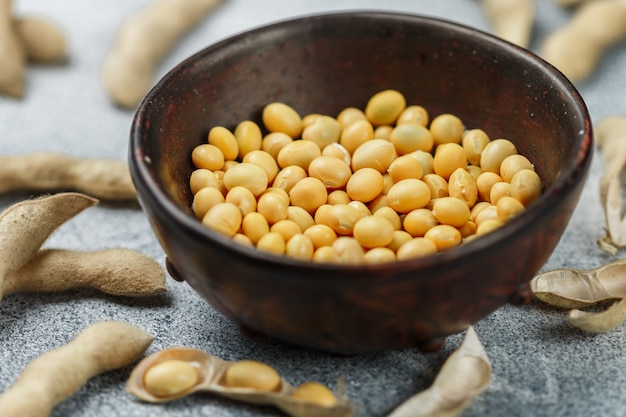 Soybeans in a clay bowl and pods on a gray concrete surface