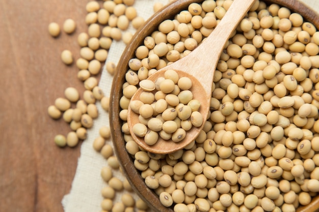 Soybeans in wooden bowl and spoon putting on linen and wooden background.