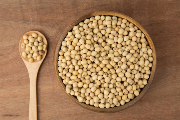 Soybeans in wooden bowl and spoon on wooden background.