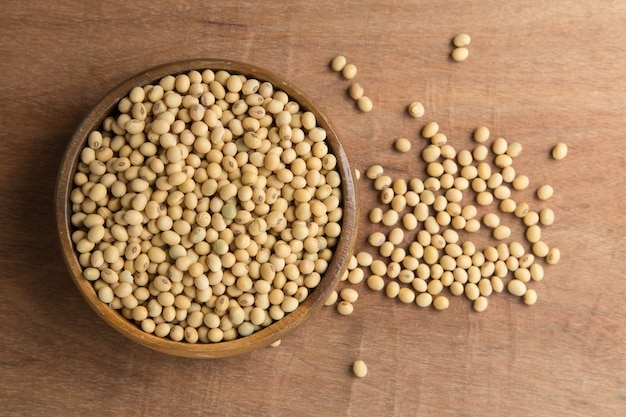 Soybeans in wooden bowl on wooden background.