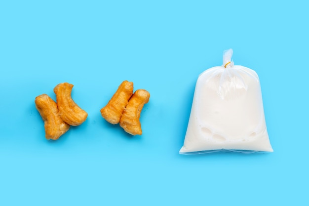 Soymilk in plastic bag with deep-fried dough stick or chinese bread stick on blue surface