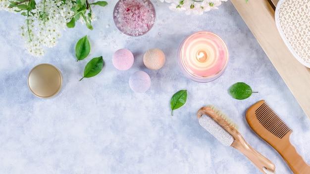 木製のテーブルにバスソルトと美容トリートメント製品を備えたスパとバスアクセサリー。ウェルネスのコンセプト