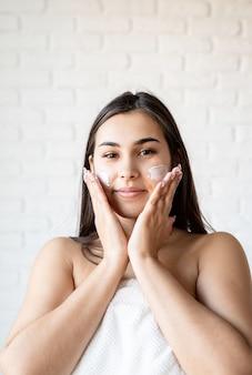 Спа и красота. счастливая красивая кавказская женщина в банных халатах, наносящая крем для лица на лицо