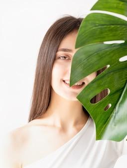 스파와 아름다움. 자기 관리 및 피부 관리. 그녀의 얼굴 앞에 녹색 몬스 테라 잎을 들고 아늑한 옷에 행복 한 아름 다운 여자