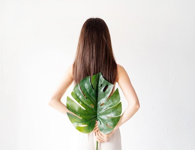 스파와 아름다움. 자기 관리 및 피부 관리. 녹색 몬스 테라 잎, 후면보기를 들고 아늑한 옷에 행복 한 아름 다운 여자