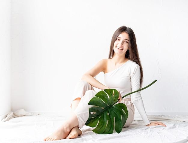 스파와 아름다움. 자기 관리 및 피부 관리. 녹색 monstera 잎을 들고 아늑한 옷에 행복 한 아름 다운 여자