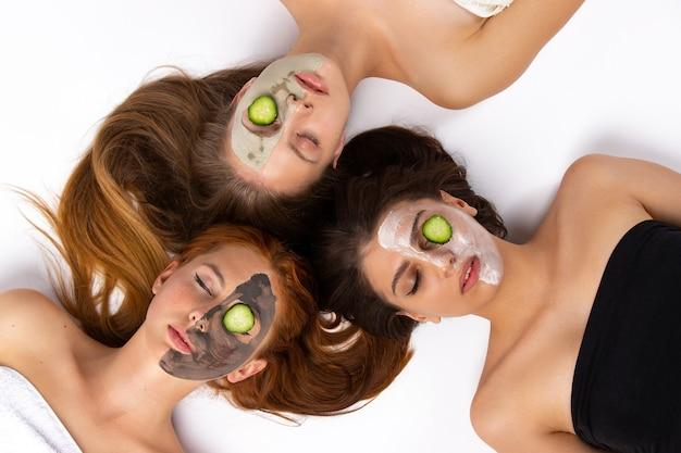 스파 및 뷰티 세 명의 여성이 서로 다른 얼굴 하프 마스크를 착용하고 건강한 피부와 바닥에 누워 있습니다.