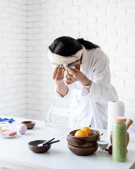 스파 및 웰빙 개념. 자가 관리. 스파 절차를 하 고 페이셜 마스크를 만드는 흰색 목욕 가운에 여자의 초상화
