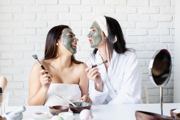 스파 및 웰빙 개념. 자가 관리. 재미 얼굴 마스크를 적용 두 아름 다운 여자