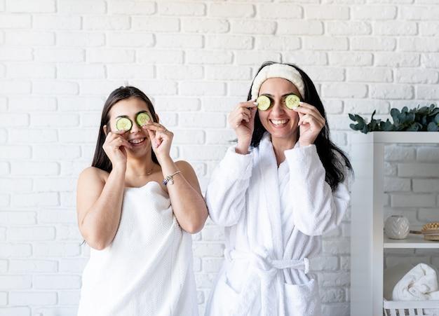 스파 및 웰빙 개념. 자가 관리. 오이로 눈을 덮고있는 스파 절차를하고있는 두 명의 아름다운 여성