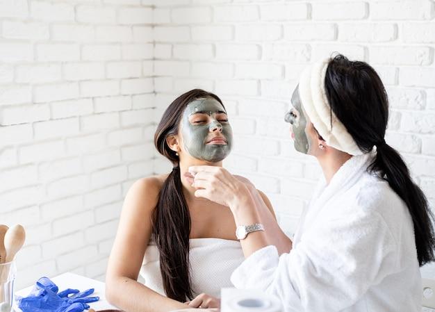 스파 및 웰빙 개념. 자가 관리. 재미 얼굴 마스크를 적용 목욕 가운에 두 아름다운 여성