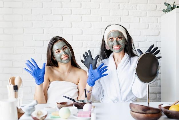 스파 및 웰빙 개념. 자가 관리. 재미 얼굴 마스크를 적용 장갑에 두 아름 다운 여자