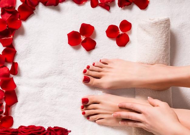 Спа и велнес. женские ноги с лепестками роз на махровом полотенце.