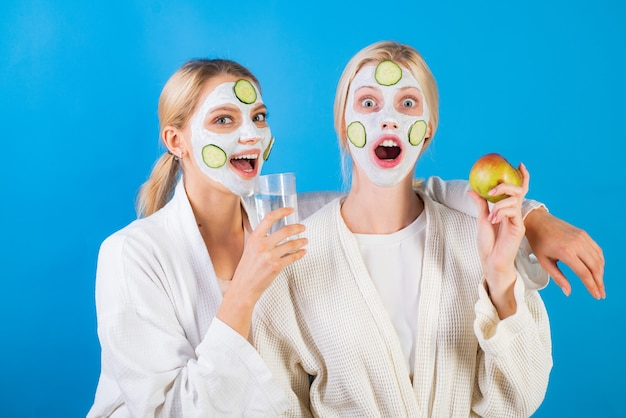 スパとウェルネス。粘土の顔のマスクを作るガールフレンド姉妹。アンチエイジングマスク。美しいまま。すべての年齢のためのスキンケア。キュウリのスキンマスクを楽しんでいる女性。水を飲むと果物を食べる。健康の概念。