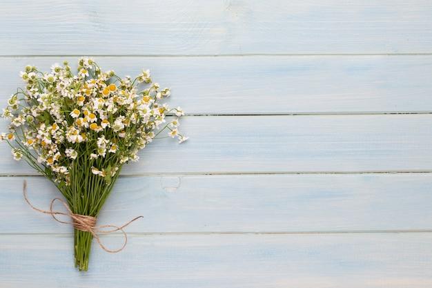 スパアロマテラピーの背景、シンプルなカモミールの花で飾られたさまざまな美容製品のフラットレイ。