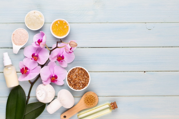 Спа ароматерапия фон, плоская планировка различных косметических средств, украшенных простыми цветами орхидеи.
