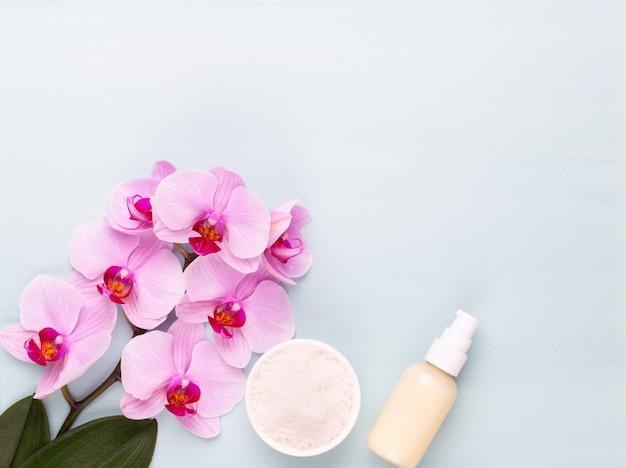 スパのアロマセラピーの背景、シンプルな蘭の花で飾られたさまざまな美容ケア製品のフラットレイアウト。