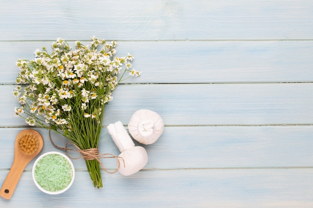 Spa aromatherapy background, flat lay of various beauty care products decorated with simple chamomile flowers.