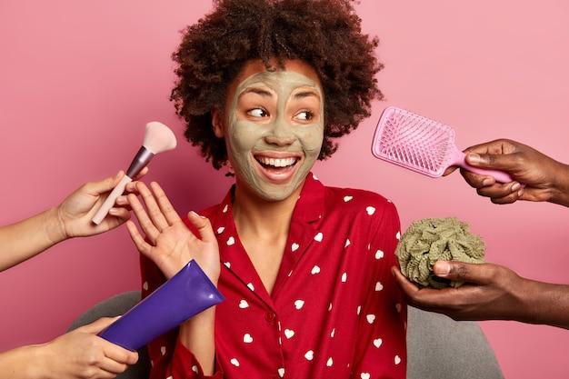 自宅のスパ。嬉しい暗い肌の若い女性は手のひらを上げ、赤いパジャマを着て、喜んで脇に見え、粘土マスクを適用します