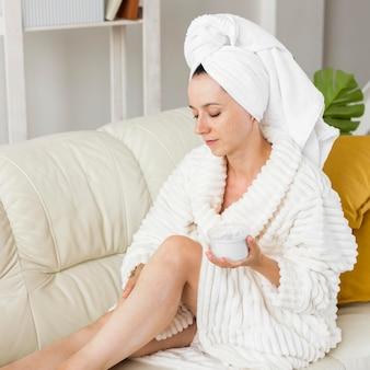 自宅の女性がクリームを適用するスパ