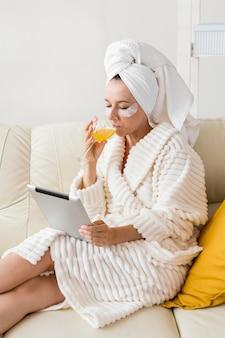 Спа дома женщина пьет здоровый сок