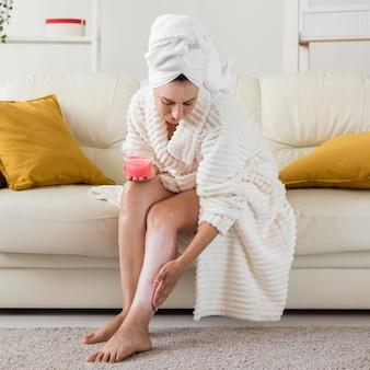 Спа дома женщина в халате, применяя крем