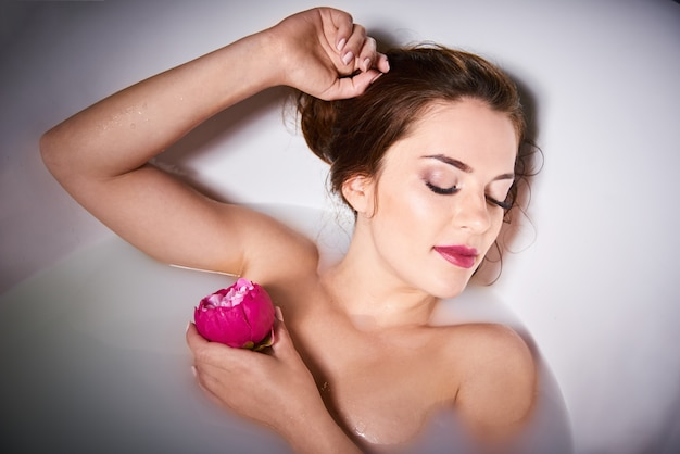 自宅でスパ-女性はバスルームでリラックスします。ミルク付きのバスタブで美しい白人女性。明るい背景にお風呂でリラックスできる魅力的な女の子。肌の世話をする若い女性