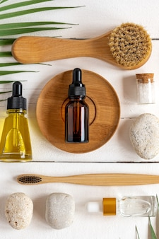 Фон спа. натуральная органическая спа-косметика, экологически чистые аксессуары для ванных комнат, тропические листья. концепция ухода за кожей на белом фоне деревянных. плоская планировка, вид сверху