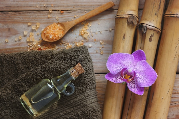 Spa background with bamboo, bath salt, massage oil, orchid flower and towel.