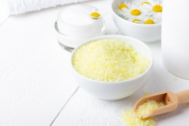 Спа фон с желтой морской солью, натуральным кремом и ромашкой для ванны на белом деревянном столе