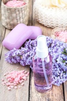 満開のライラックとエッセンシャルオイルまたは花hydrolat、化粧品のアロマ石鹸のボトルとスパの背景