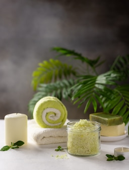 Spa background with sea salt, solid soap, candles and bath towels on a background of green palm leaves. beauty spa treatment and relax concept.