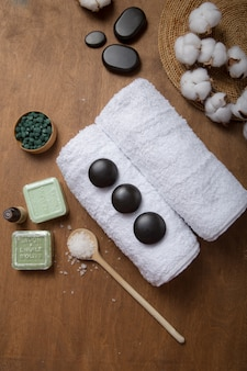Spa, beauty cosmetics and body care treatment concept with copy space. creative top view flat lay composition with bath accessories green spirulina, stones, oil, sea salt, soap