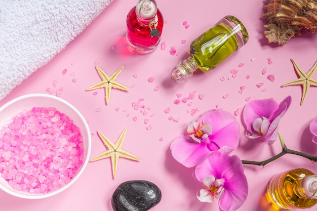 Spa beauty cosmetics on pink table from above