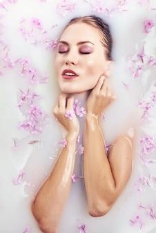 우유 목욕, 스파 및 스킨 케어 개념에서 목욕 스파 뷰티 모델 소녀. 우유 목욕에서 편안한 꽃 화 환에 완벽 한 슬림 바디와 부드러운 피부, 뷰티 젊은 여자.