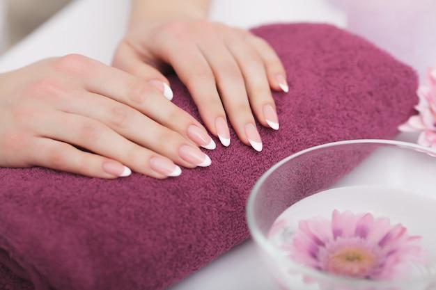スパビューティーサロン。マニキュアの前に手風呂に浸る完璧な自然の爪で女性の手のクローズアップ。水の透明なボウルで完璧な爪を洗う女。ネイルケア。高解像度