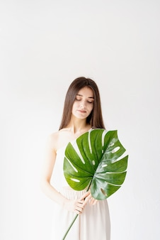 Spa and beauty. self care and skin care. happy beautiful woman in cozy clothes holding a green monstera leaf