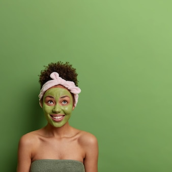Spa beauty treatment and skin care concept. positive female applies face peeling mask, stays young and beautiful concentrated above with broad smiles, wears headband, poses over green wall copy space