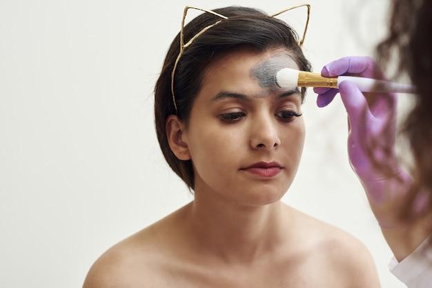 스파 뷰티 트리트먼트, 스킨 케어. 스파 살롱에서 미용사에 의해 얼굴 관리를 받고 여자.