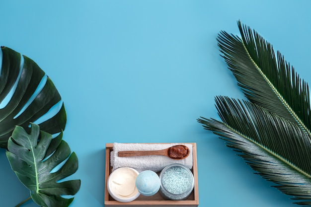 Spa. body care items on blue with tropical leaves.