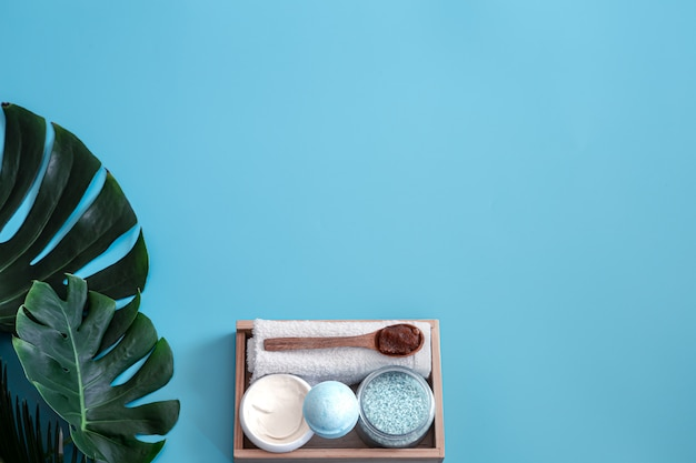 スパ。熱帯の葉と青色の背景にボディケアアイテム。夏のアクセサリー。テキストのためのスペース。