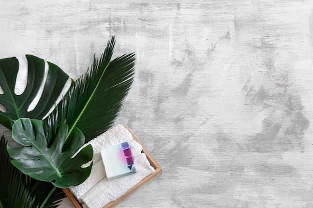 スパ。熱帯の葉と白い背景の上のボディケアアイテム。夏のアクセサリー。テキストのためのスペース。