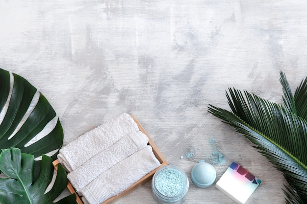 Spa. body care items on white with tropical leaves.