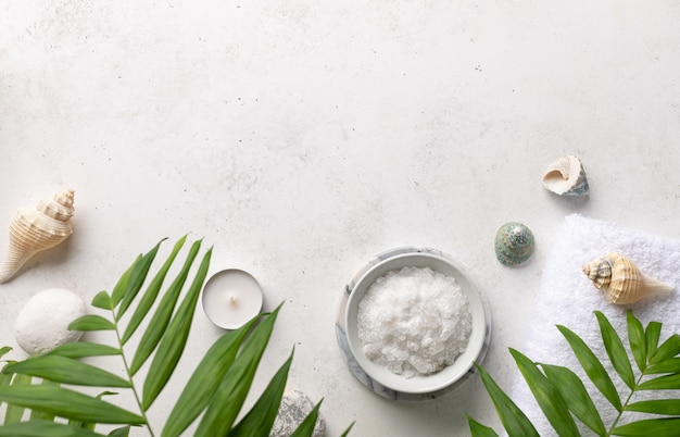 Spa border with natural sea salt in a bowl, candles, shells and green palm leaves on a white stone background relaxation and zen like concept ,