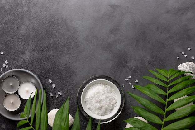 Spa border with natural sea salt in a bowl, candles, stones and green palm leaves on a dark stone background spa wellness relax concept ,