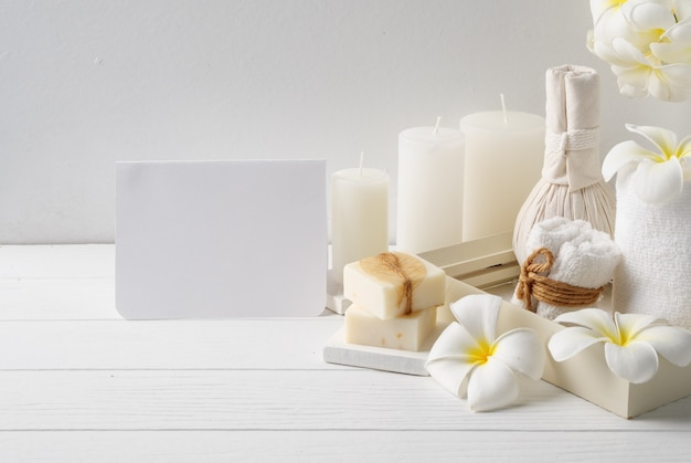 Приглашение на спа-карту с массажным салфеткой, цветок флумерии в вазе, кокосовое кофейное мыло, белые полотенца и свеча на белом фоне деревянного стола Premium Фотографии