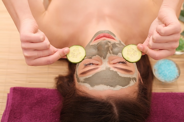 Spa. care facial. funny young girl with a mask for skin face and cucumbers