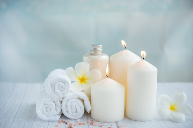 Spa coconut products on light wooden surface. composition with towels, flowers and salt, candle  on massage table in spa salon
