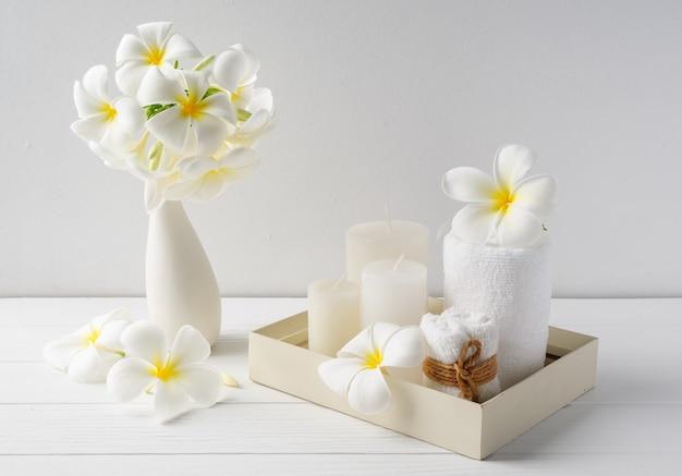 Спа-композиция с красивыми цветами плюмерии, белыми свечами и полотенцами на деревянном подносе на внутренней поверхности белого деревянного стола