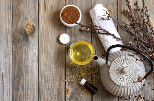 Спа-композиция в деревенском стиле с чайником, натуральным средством по уходу за телом на деревянной поверхности.